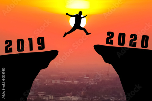 Foto auf Gartenposter Koralle Silhouette young man jumping from 2019 to 2020 year