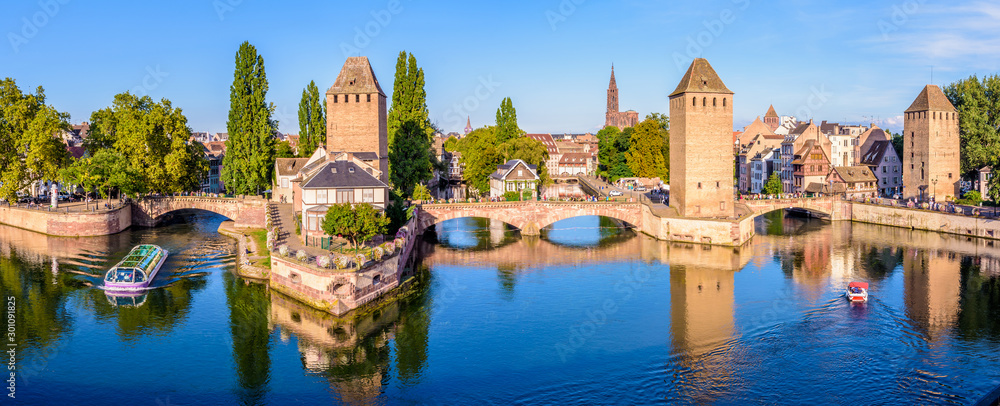 Fototapety, obrazy: Panoramic view of the Ponts Couverts on the river Ill at the entrance of the Petite France historic quarter in Strasbourg, France, with a tour boat and an electric renting boat cruising on the canals.