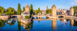 canvas print picture - Panoramic view of the Ponts Couverts on the river Ill at the entrance of the Petite France historic quarter in Strasbourg, France, with a tour boat and an electric renting boat cruising on the canals.