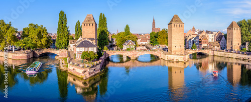 Fotografija  Panoramic view of the Ponts Couverts on the river Ill at the entrance of the Petite France historic quarter in Strasbourg, France, with a tour boat and an electric renting boat cruising on the canals