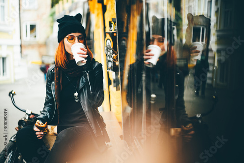 Canvas Print Red hair woman in black rock style leather jacket drinking takeaway coffee at the autumn city