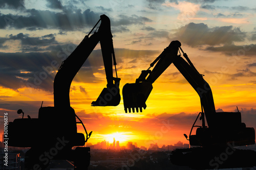 Obraz Silhouettes two excavator with sunlight background of sunset in cityscape - fototapety do salonu