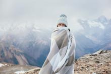 Teenage Girl Wrapped In Plaid Blanket Standing On Mountain Peak