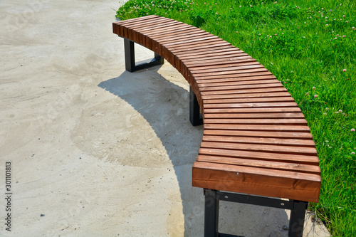 Photo Curved wooden bench in the park. Empty bench in the summer park.