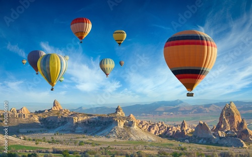 Montgolfière / Dirigeable Colorful hot air balloons fly in blue sky over amazing valleys with fairy chimneys in Cappadocia, Turkey