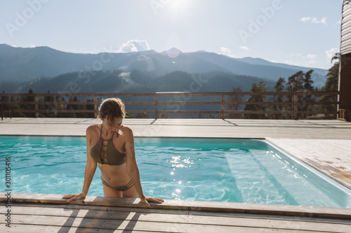 Fotografía  Young woman spending vacation in swimming pool with mountain landscape