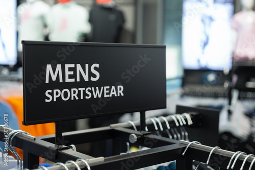 Fotomural  Close up of MENS SPORTSWEAR Sign in the sports clothes superstore