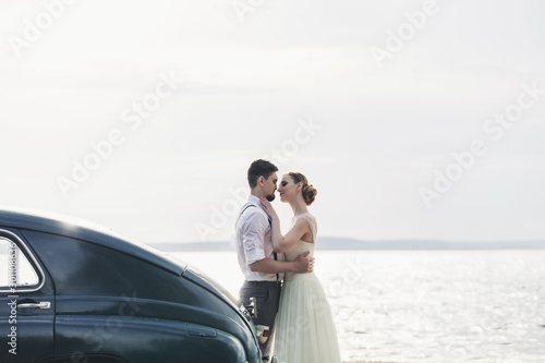 Leinwand Poster Happy bride and groom standing near car on shore sea