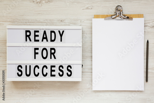 Fotomural  'Ready for success' words on a modern board, clipboard with blank sheet of paper on a white wooden background, top view