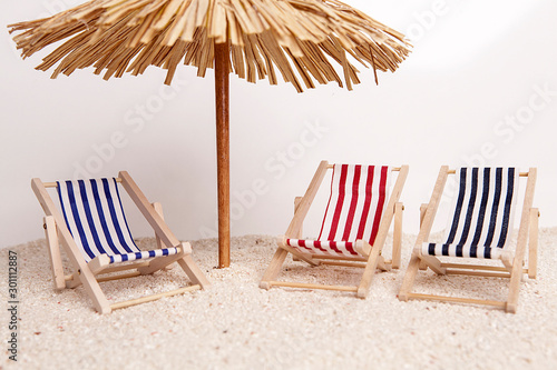 Toy chaise longue and sun umbrella on sandy beach on sunny day at the white background Poster Mural XXL