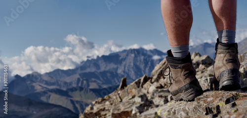 Fototapeta Close up view of high trekking boots and male legs on stony mountain top; dangerous hiking route with professional reliable equipment; wide panorama for banner; space for text obraz