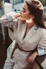 Beautiful Stylish Girl Posing In Beige Suit And Beret On Urban Roof