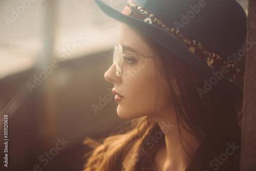 Obraz attractive elegant woman posing in hat, eyeglasses and brown jacket on roof - fototapety do salonu