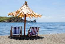 Toy Chaise Longue And Sun Umbrella On Sandy Beach On Sunny Day At The Blue Sea Background. Relaxation Concept.