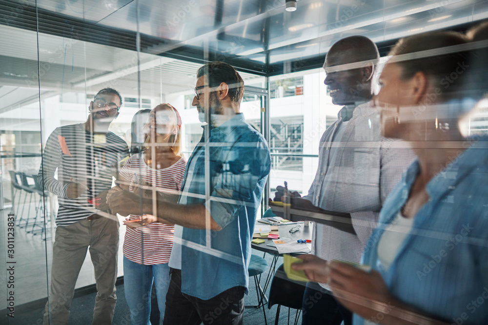 Fototapeta Smiling businesspeople brainstorming on a glass wall in an offic