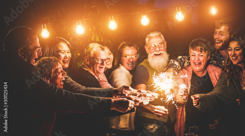 Fotografia Happy family celebrating with sparkler fireworks on new year's eve - Focus on le
