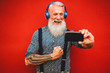 canvas print picture - Senior hipster man using smartphone app for creating playlist with music - Trendy tattoo guy having fun with mobile phone technology - Tech and joyful elderly lifestyle concept - Focus on face