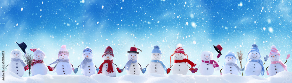 Fototapeta Merry Christmas and happy New Year greeting card with copy-space.Many snowmen standing in winter Christmas landscape.Winter background