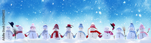 Fototapeta Merry Christmas and happy New Year greeting card with copy-space.Many snowmen standing in winter Christmas landscape.Winter background obraz
