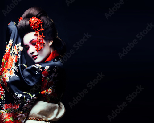 Fotografie, Tablou young pretty geisha in kimono with sakura and decoration