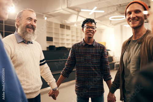 Group of happy people standing holding hands and smiling to each other during business training at office