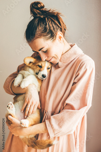 Smiling young woman embracing corgi pappy with closed eyes Canvas Print