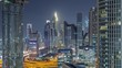 Dubai Financial Centre district with illuminated modern skyscrapers night timelapse. Aerial view from Downtown with traffic on streets and intersection