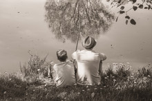 Back View Of Happy Family On Summer Vacations Concept. Father And Son Fishing Together At River Bank At Scenic Landscape Background Of Fresh Green Grass And Blue Calm Water. Horizontal Sepia Photo.