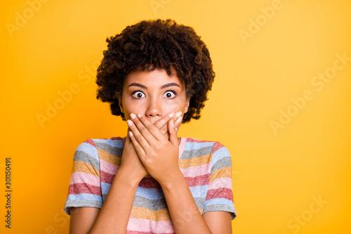 Fototapeta Closeup photo of beautiful dark skin lady looking eyes full fear calm herself hiding mouth wear casual stylish striped t-shirt isolated yellow background obraz na płótnie