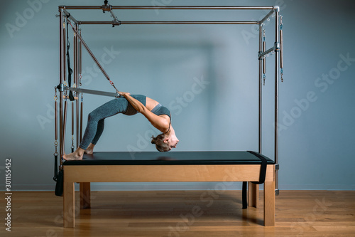 Tela Pilates woman in a Cadillac reformer doing stretching exercises in the gym