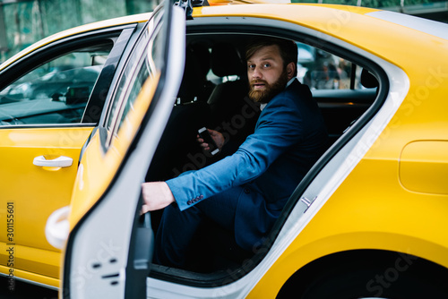Valokuvatapetti Portrait of handsome businessman looking at camera while sitting to cab for gett