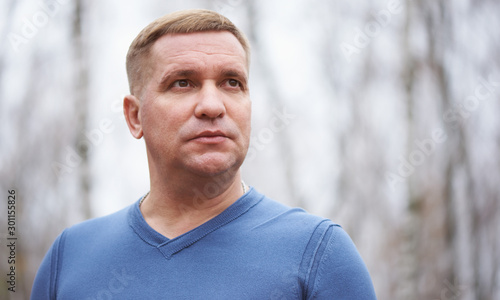 Fotomural  Middle aged man is looking away. Outdoors portrait