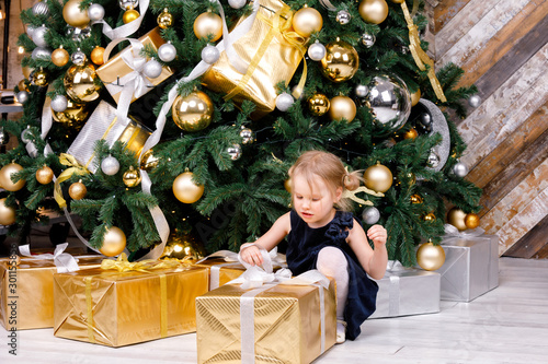 Little girl unpacking wrapped present beside decorated christmas tree at home on Canvas-taulu