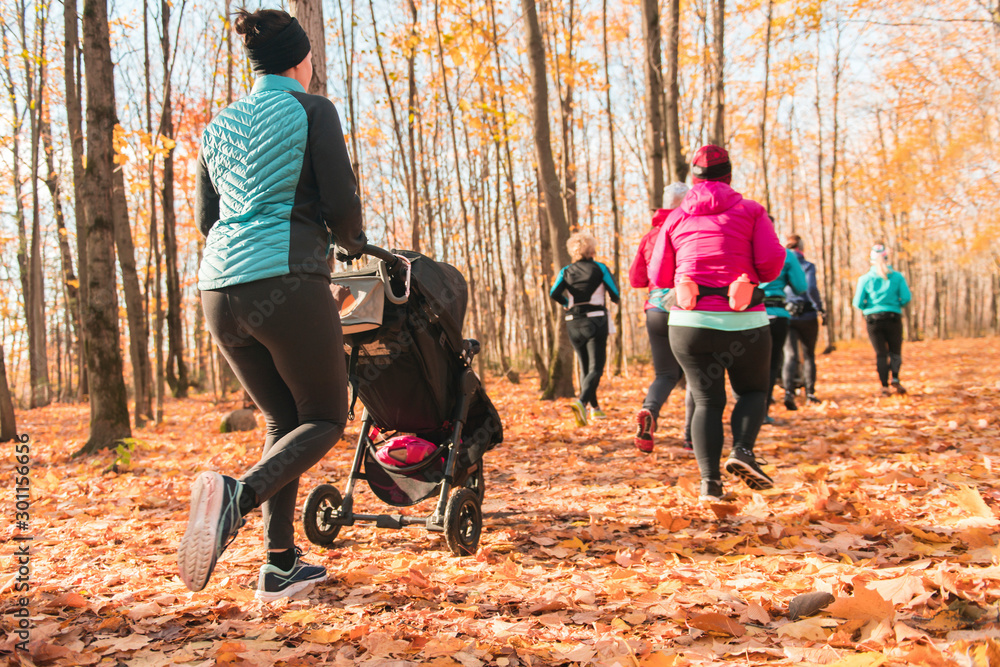 Fototapety, obrazy: Stroller woman group out running together in an autumn park they run a race or train in a healthy outdoors lifestyle concept