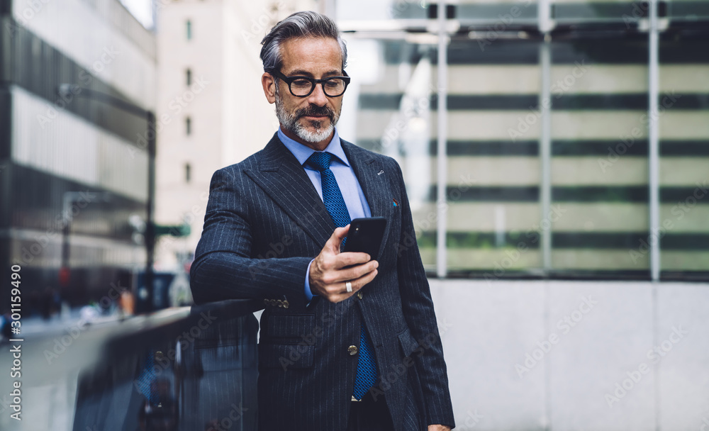 Fototapety, obrazy: Middle-aged handsome man using smartphone on urban background