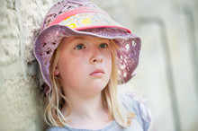 Melancholy Pretty Young Blonde Girl In Purple Hat. Blurry Background With Copy Space