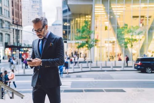Pinturas sobre lienzo  Fashionable businessman looking at smartphone on street