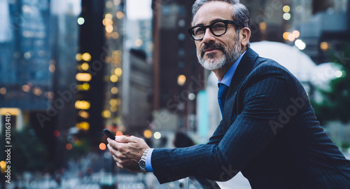 Adult businessman holding phone against background of New York street