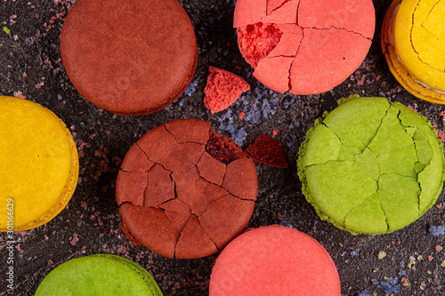 Aluminium Prints Macarons Colorful macarons cracked macaroons over on black background. Copy space