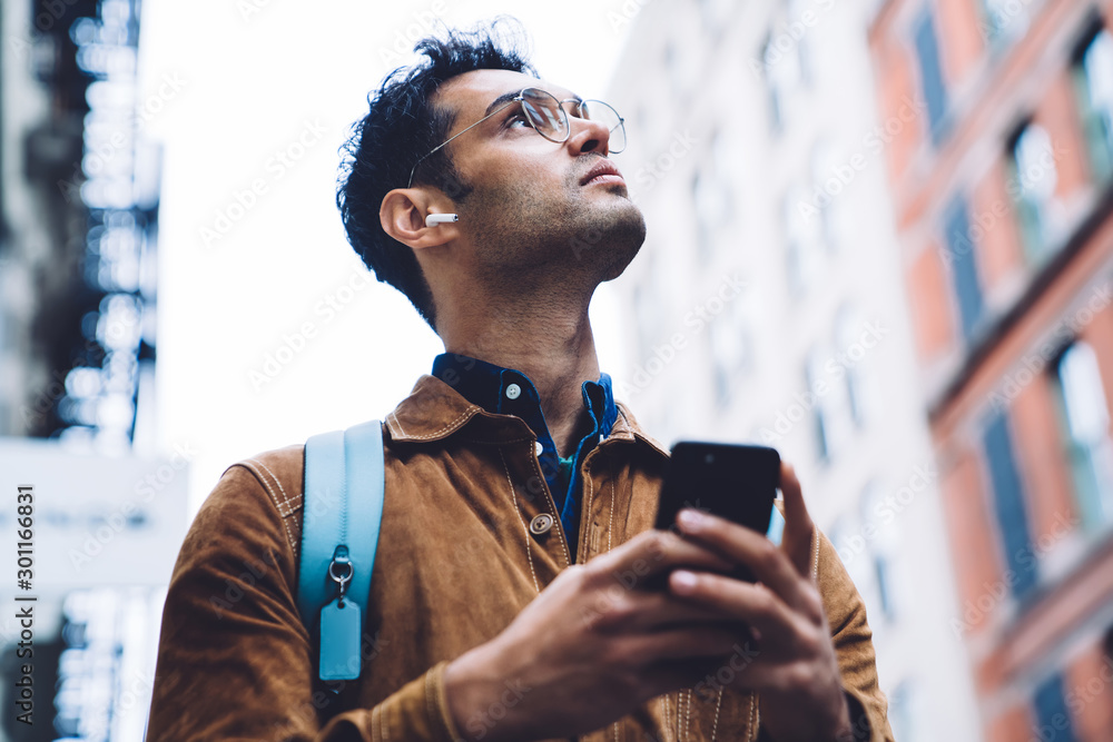 Fototapeta Hispanic young man in eyeglasses standing on street with smartphone