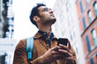 Hispanic young man in eyeglasses standing on street with smartphone