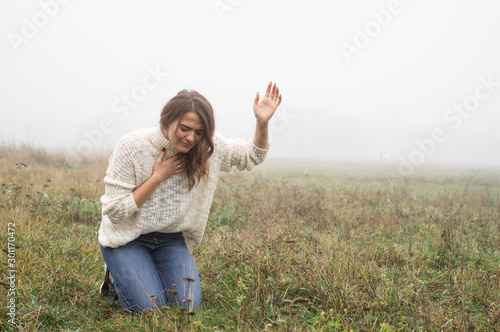 Fototapeta Girl closed her eyes on the knees, praying in a field during beautiful fog
