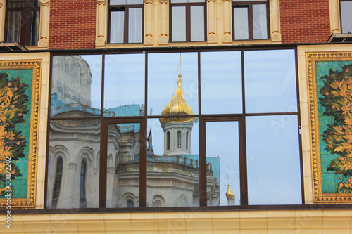 Photo sur Aluminium Con. Antique Old church reflection on modern building window. City scene with cathedral facade mirroring on urban windows in Moscow, Russia