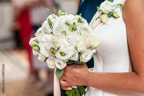 Fotomural  Groom and bride holding hands on the bouquet of flowers