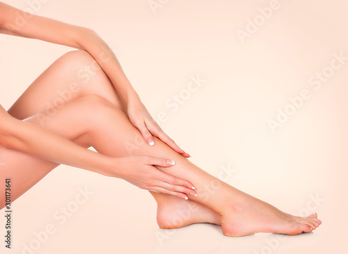 Pinturas sobre lienzo  Woman sitting on the floor and touching her leg by hands, Beauty and skin care c