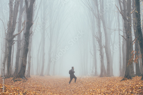 Montage in der Fensternische Lachs Man in tall forest in fog or mist. Dark spooky forest with man wondering in the nature with tourist bag