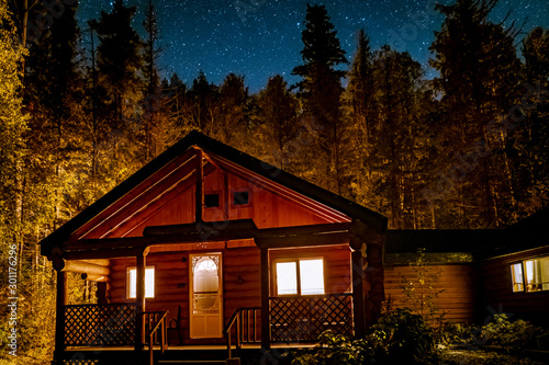 Leinwand Poster wooden cabin cottage at night under the stars in the wood forest of Canada