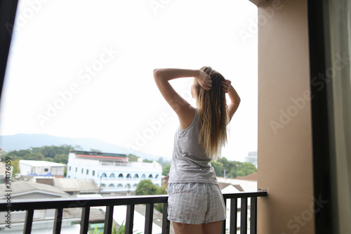 Fotomural  Young european girl wearing summer pajamas standing on balcony and looking at buildings in background