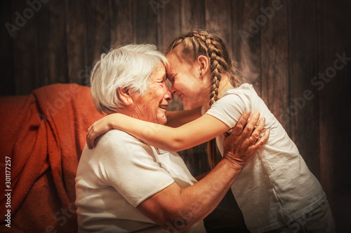 Fotografiet grandmother plays with her granddaughter, depict a plane, hug, time with relativ