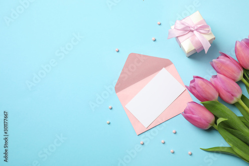 Flat lay composition with tulips and card on light blue background, space for text. Happy Mother's day